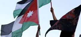"Members of Al-Abbad hold Palestinian and Jordanian national flags, and flag read ""Gaza"" during a rally in Amman"